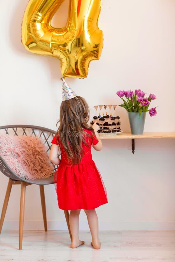 Lycklig liten flicka som hemma firar den fjärde födelsedagen royaltyfri foto