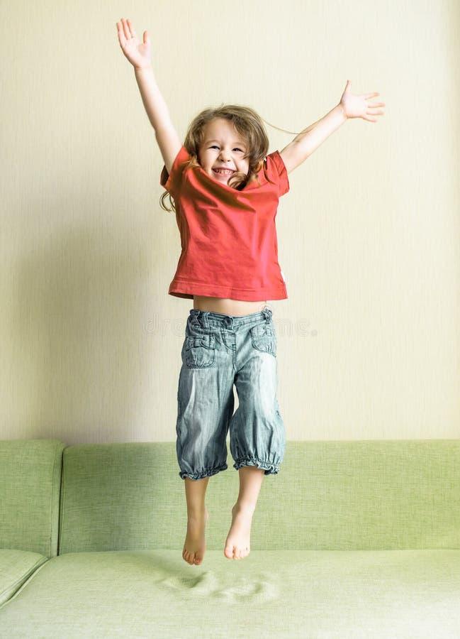 Lycklig liten flicka som hemma spelar och hoppar royaltyfri foto