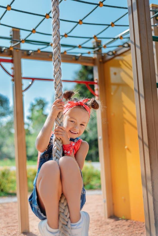 Lycklig liten flicka som klättrar det gymnastiska repet på lekplatsen royaltyfria bilder