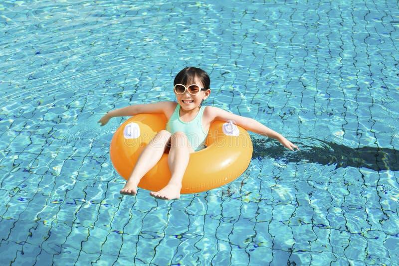 Lycklig liten flicka som kopplar av och simmar i pölen royaltyfria foton