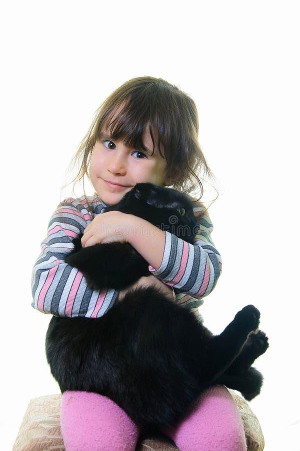 Lycklig liten flicka som kramar den älskvärda kattungen arkivfoton