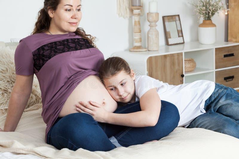 Lycklig liten flicka som kramar den gravida moderbuken, medan lägga på sängen i sovrum royaltyfria foton