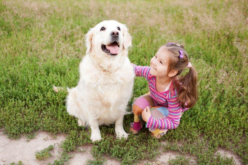 Lycklig liten flicka som kramar en hund arkivbild