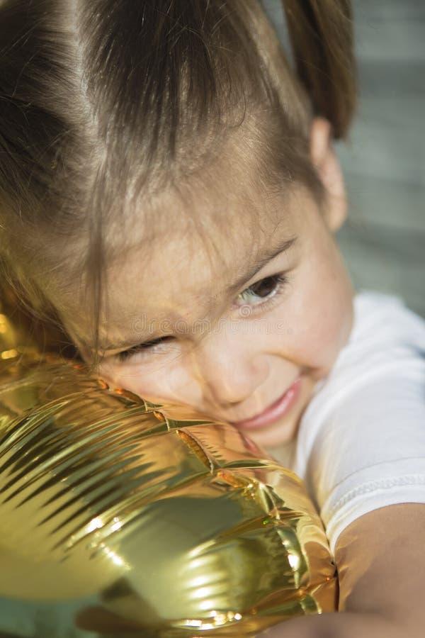 Lycklig liten flicka som kramar med den guld- ballongen arkivbild
