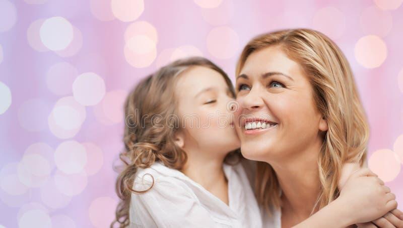 Lycklig liten flicka som kramar och kysser hennes moder royaltyfria bilder