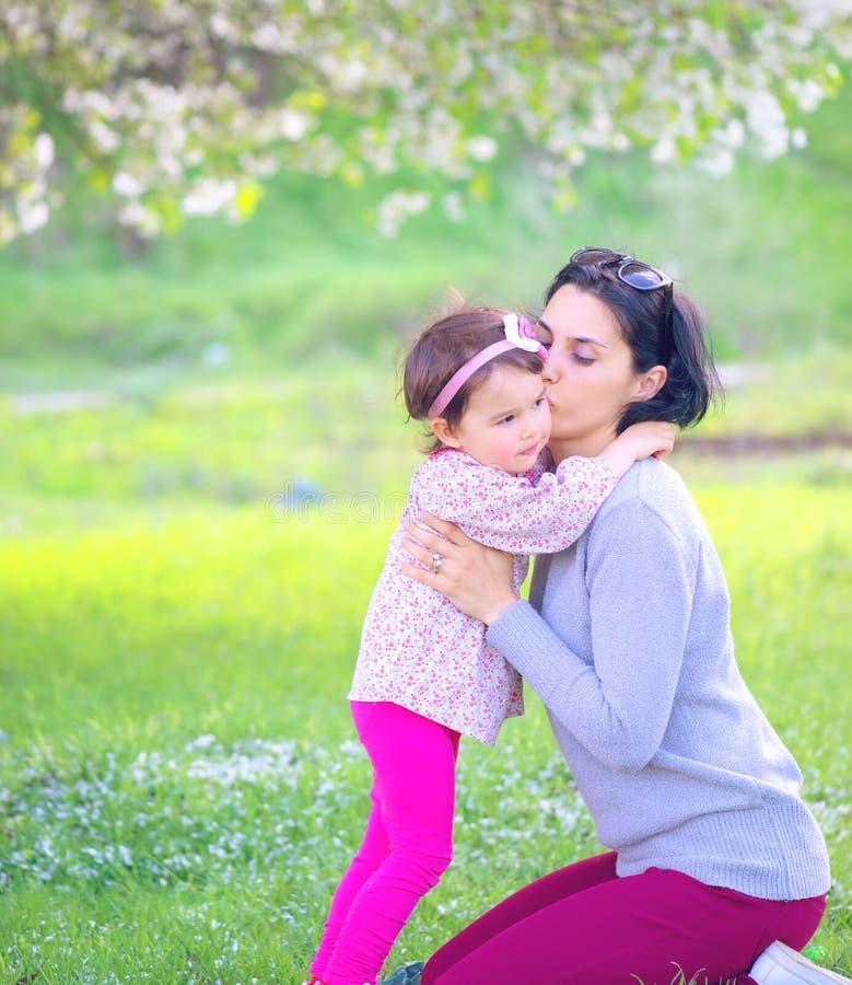 Lycklig liten flicka som kramar och kysser hennes moder royaltyfria foton