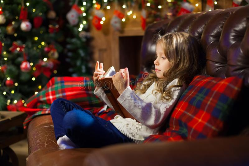 Lycklig liten flicka som läser en berättelsebok förbi på soffan i en slags tvåsittssoffa arkivbild