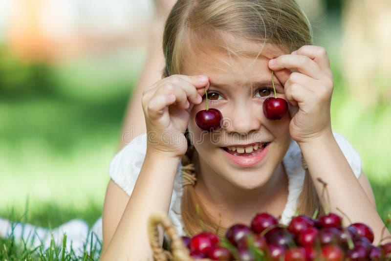 Lycklig liten flicka som ligger nära trädet med en korg av körsbär arkivbild