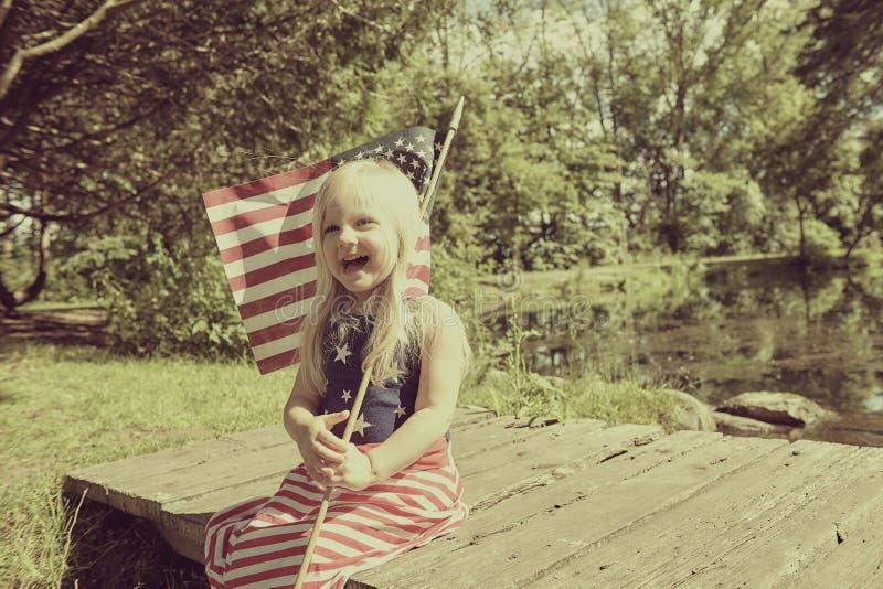 Lycklig liten flicka som poserar med amerikanska flaggan arkivfoton