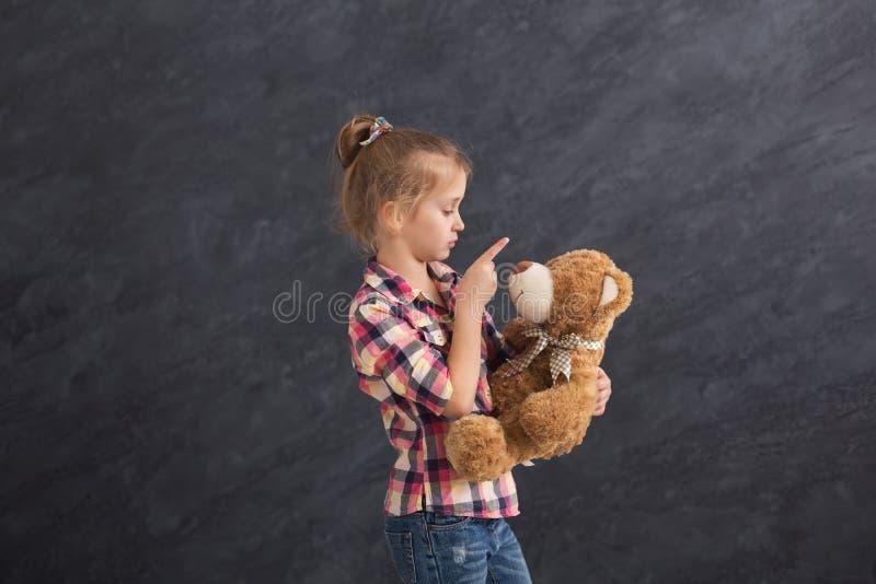 Lycklig liten flicka som poserar med nallebjörnen på grå bakgrund royaltyfri fotografi