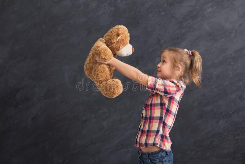 Lycklig liten flicka som poserar med nallebjörnen på grå bakgrund arkivfoton