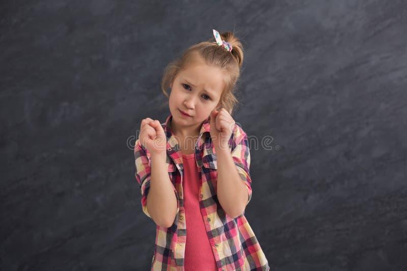 Lycklig liten flicka som poserar på grå bakgrund royaltyfri foto