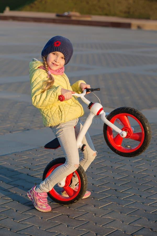 Lycklig liten flicka som rider den första cykeln royaltyfria bilder
