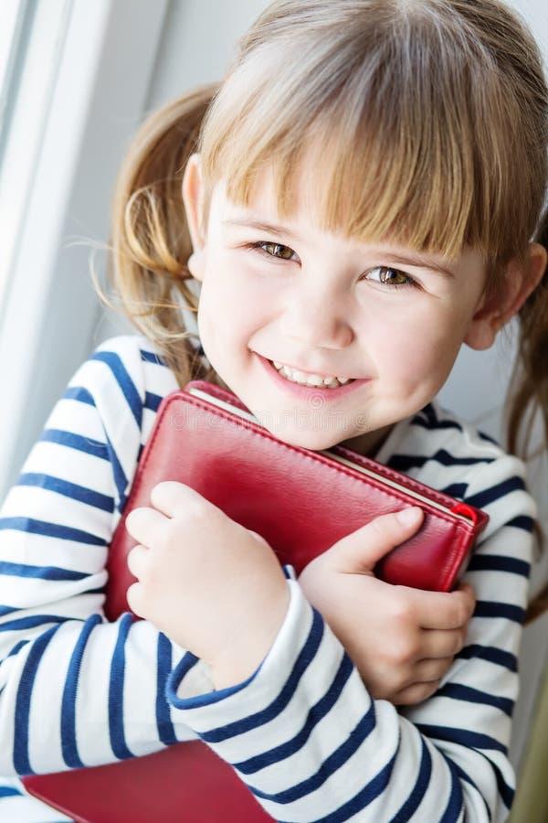 Lycklig liten flicka som rymmer en bok fotografering för bildbyråer