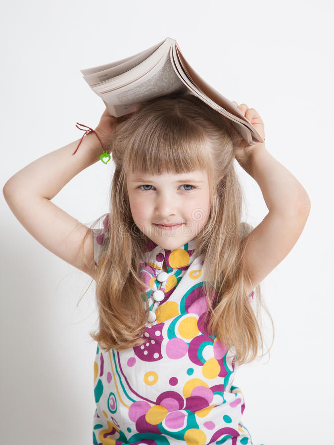 Lycklig liten flicka som rymmer en bok royaltyfria foton