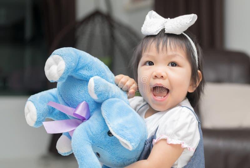 Lycklig liten flicka som spelar den elephent dockan arkivfoto
