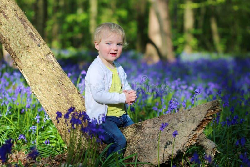 Lycklig liten flicka som spelar i blåklockaskog royaltyfri fotografi