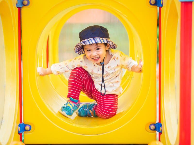 Lycklig liten flicka som spelar på lekplatsen Barn som är lyckliga, fa arkivfoton