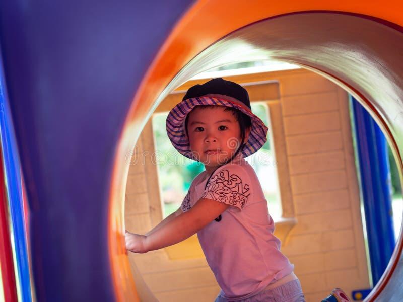 Lycklig liten flicka som spelar på lekplatsen Barn som är lyckliga, fa royaltyfri fotografi