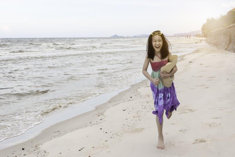Lycklig liten flicka som spelar på stranden arkivfoton