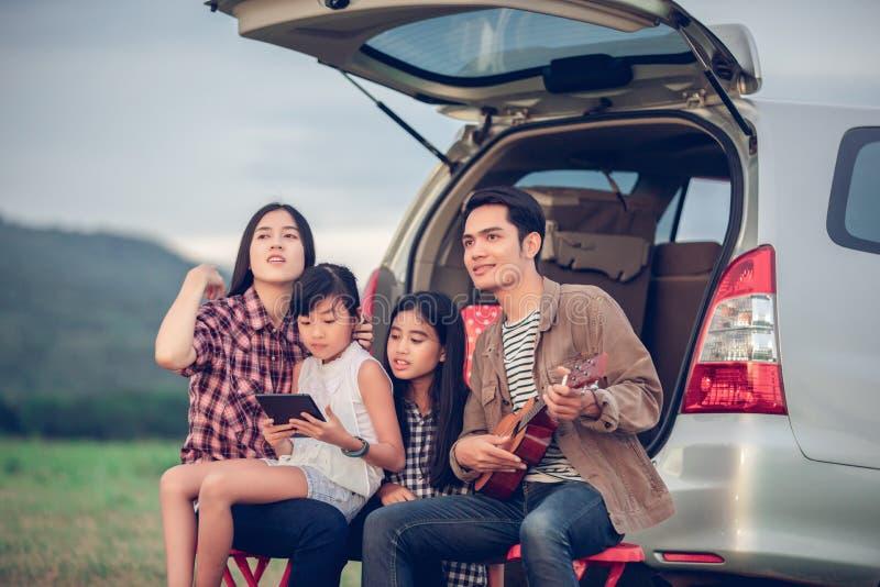 Lycklig liten flicka som spelar ukulelet med asiatiskt familjsammantr?de i bilen f?r att tycka om v?gtur och sommarsemester royaltyfri bild