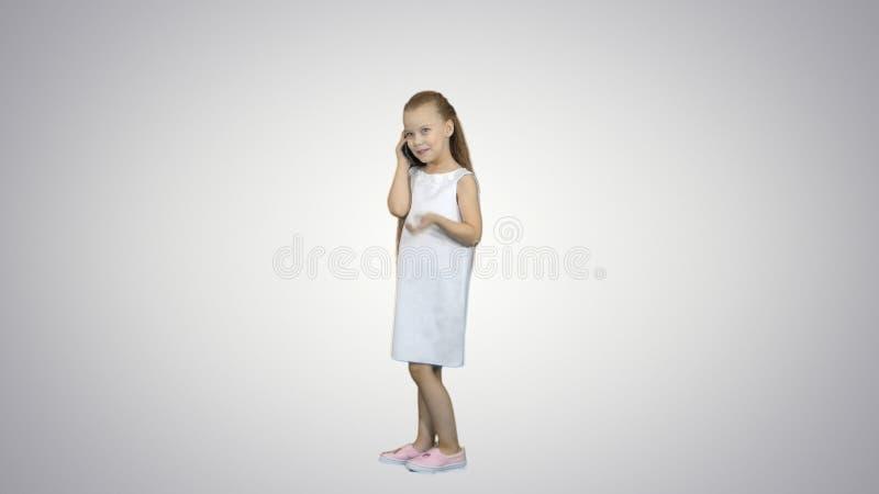 Lycklig liten flicka som talar vid mobiltelefonen på vit bakgrund arkivbilder