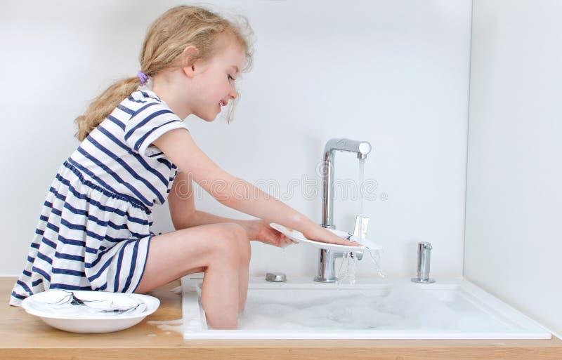 Lycklig liten flicka som tvättar disken royaltyfri bild