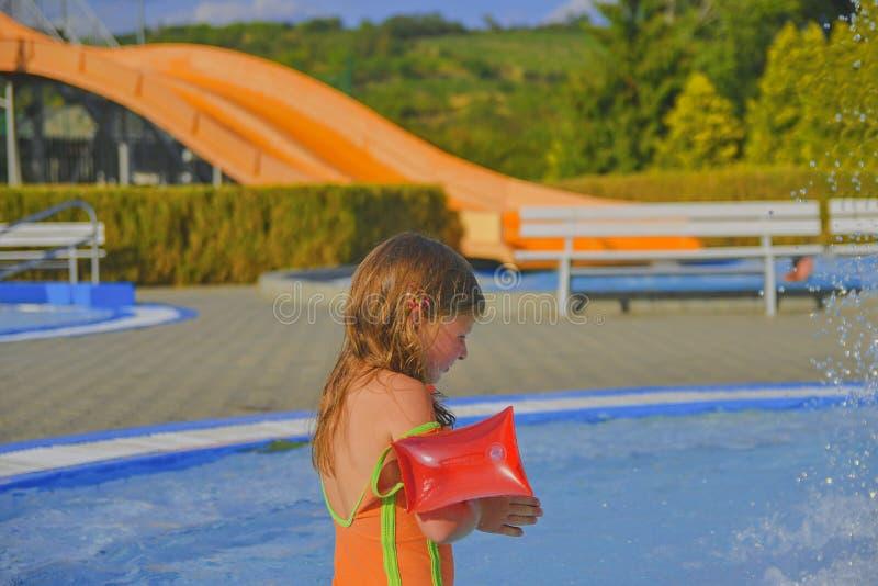 Lycklig liten flicka som tycker om sommardag i simbassängen Gullig flicka med uppblåsbara armbindlar i liten simbassäng Sommar oc arkivfoto