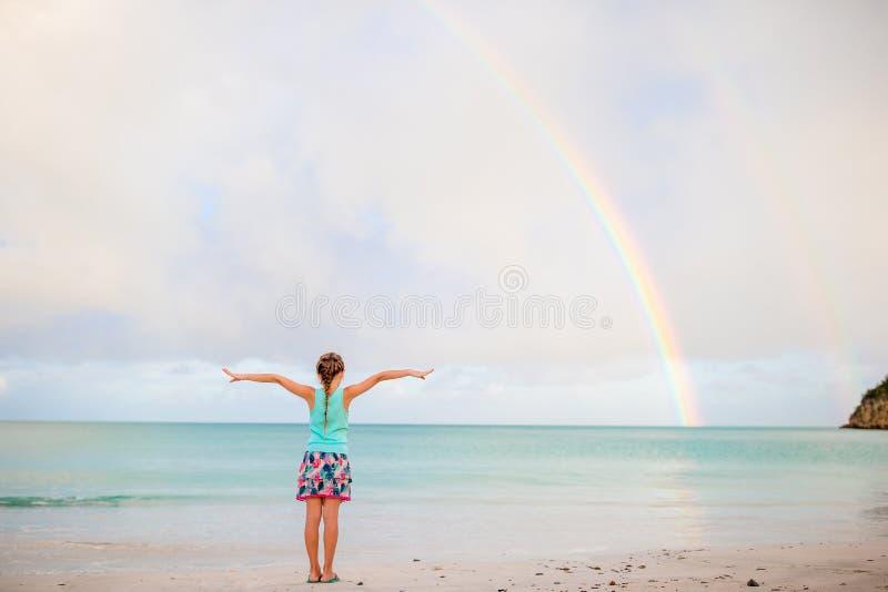 Lycklig liten flickabackgound den härliga regnbågen över havet arkivbild