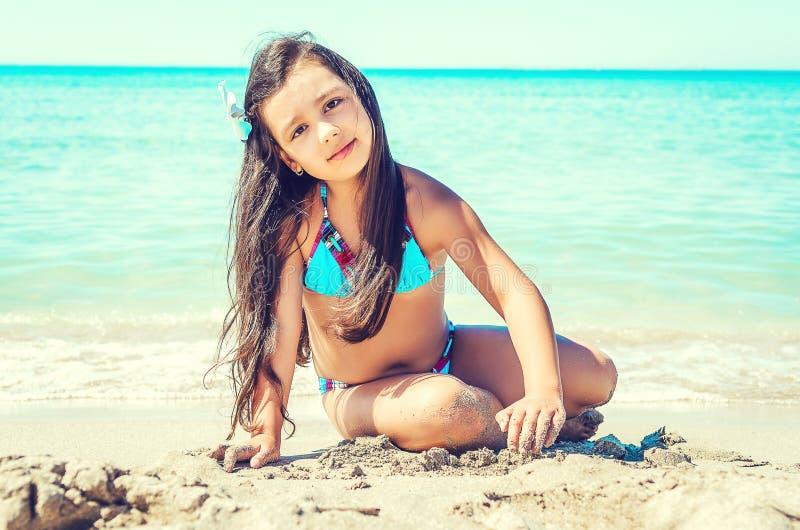 Lycklig liten flickabanhoppning på stranden royaltyfri bild