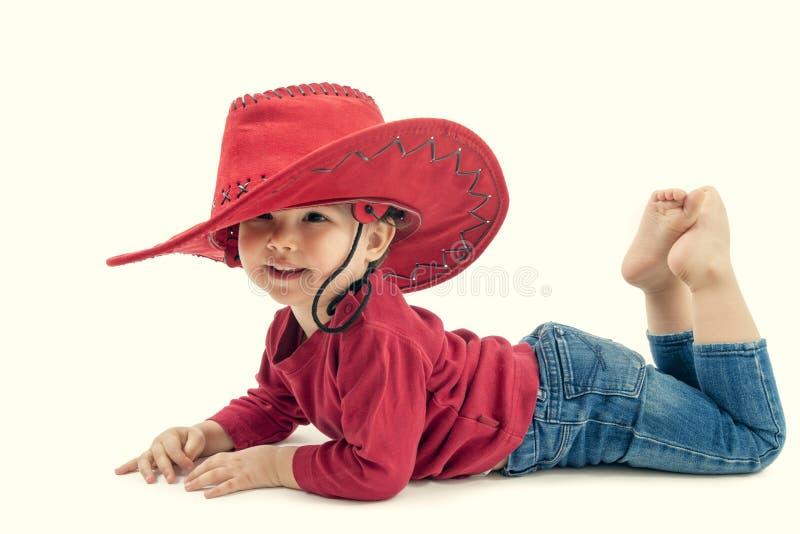 Lycklig liten flickacowboy i en röd hatt på en vit royaltyfria bilder