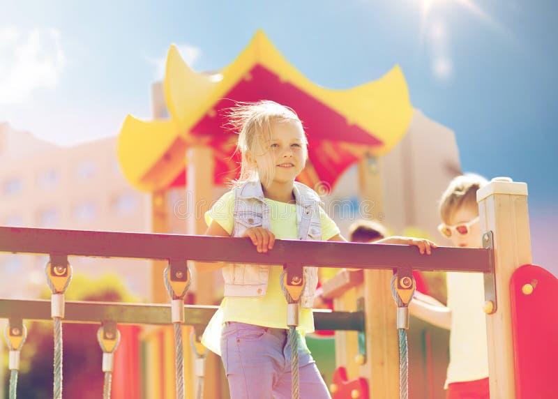 Lycklig liten flickaklättring på barnlekplats royaltyfria bilder