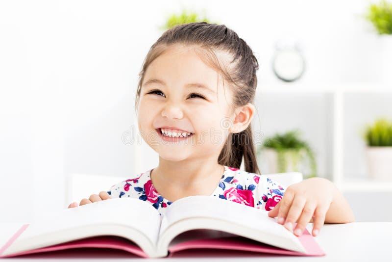 Lycklig liten flickaläsebok arkivfoto