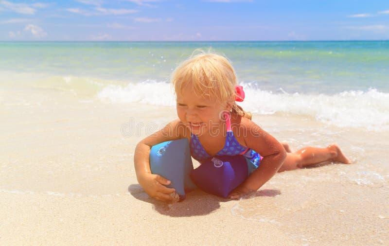 Lycklig liten flickalek med armbindlar på havet arkivfoton