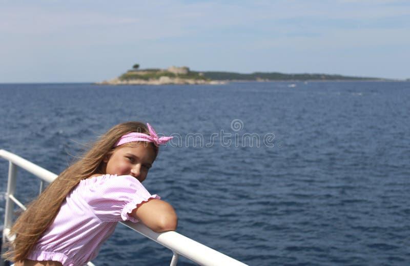 Lycklig liten flickasegling i ett fartyg som ler på havet på sommarkryssning arkivfoton