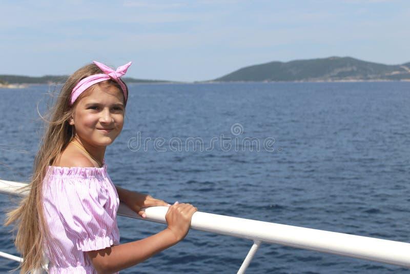 Lycklig liten flickasegling i ett fartyg som ler på havet på sommarkryssning arkivfoto
