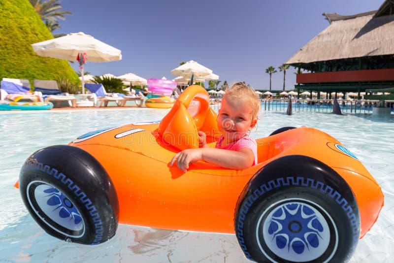 Lycklig liten flickasimning i den uppbl?sbara bilen p? sommarferier royaltyfri foto