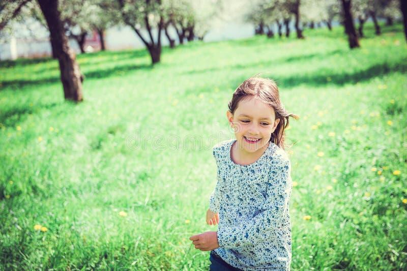 Lycklig liten flickaspring i trädgården fotografering för bildbyråer