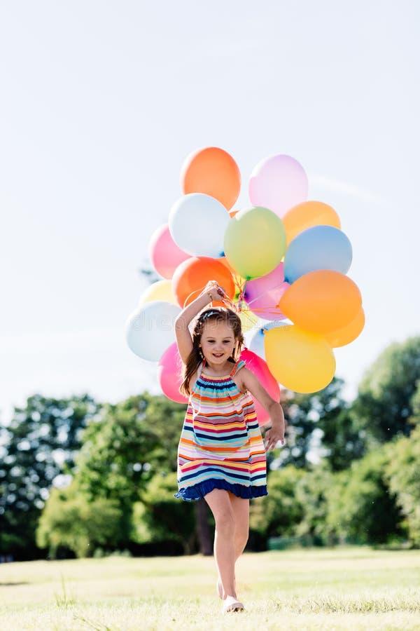 Lycklig liten flickaspring med en grupp av färgrika ballonger royaltyfria foton