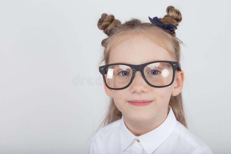 Lycklig liten flickastående, bärande vit blus och svart ramglasögon som står mot vit träbakgrund Dra tillbaka till sch arkivfoton