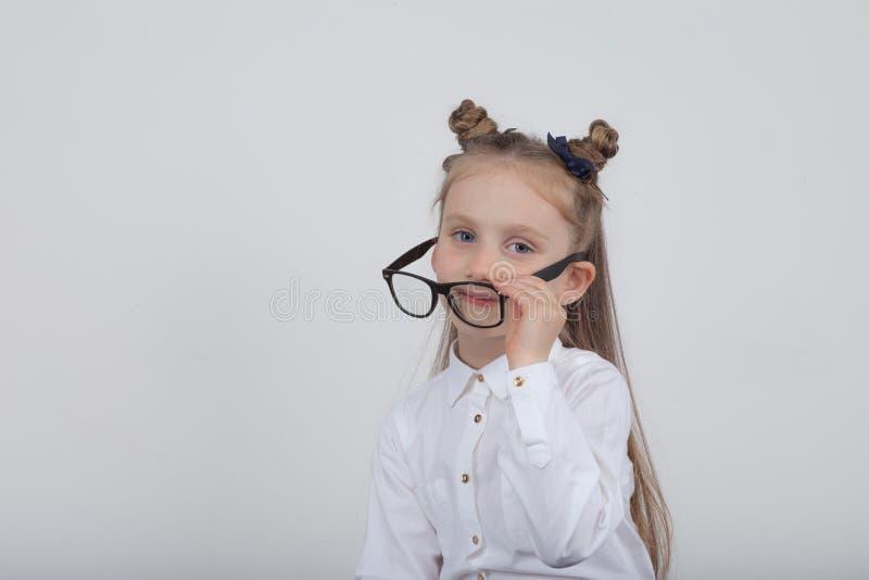 Lycklig liten flickastående, bärande vit blus och svart ramglasögon som står mot vit träbakgrund Dra tillbaka till sch royaltyfria foton