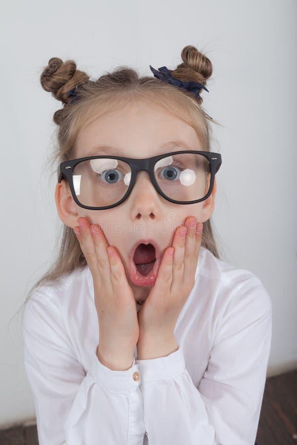 Lycklig liten flickastående, bärande vit blus och svart ramglasögon som står mot vit träbakgrund Dra tillbaka till sch royaltyfria bilder