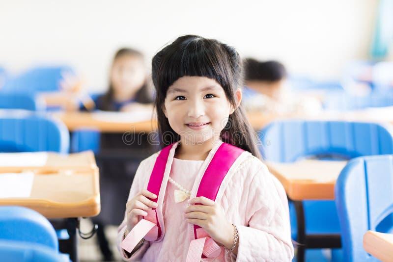 Lycklig liten flickastudent i klassrumet royaltyfria foton