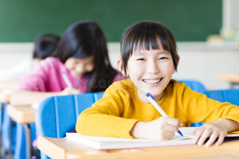 Lycklig liten flickastudent som studerar i klassrumet arkivbilder