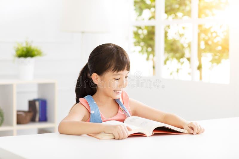 Lycklig liten flickastudie i vardagsrummet royaltyfri fotografi