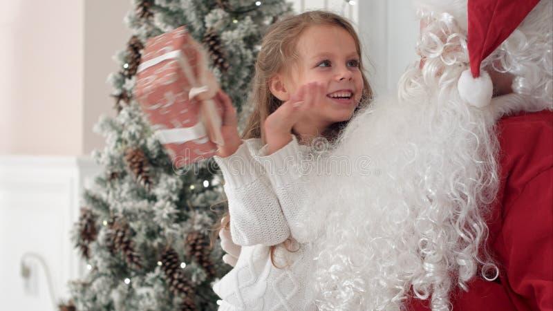 Lycklig liten le flicka som försöker att gissa vad är inom hennes julgåva från jultomten fotografering för bildbyråer