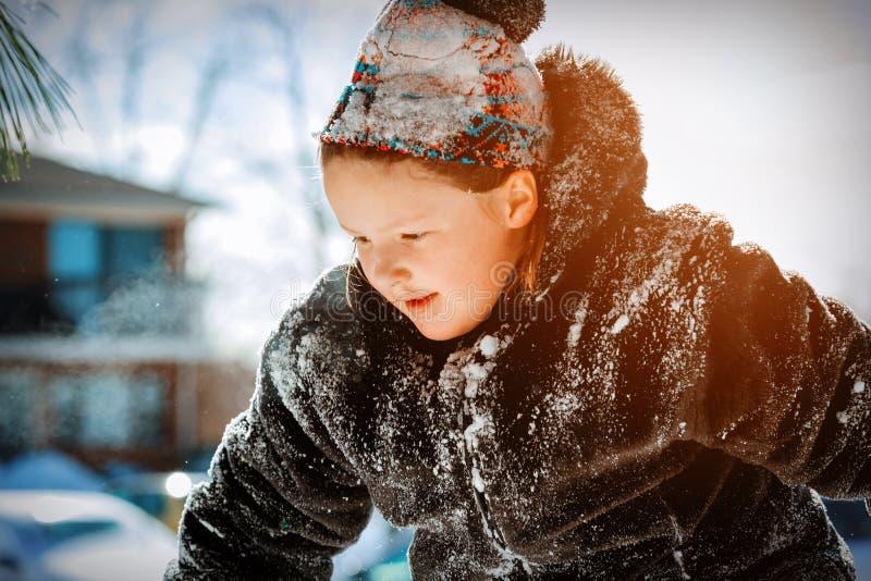 Lycklig liten le flicka utomhus i de insnöade vinterkläderen royaltyfria bilder