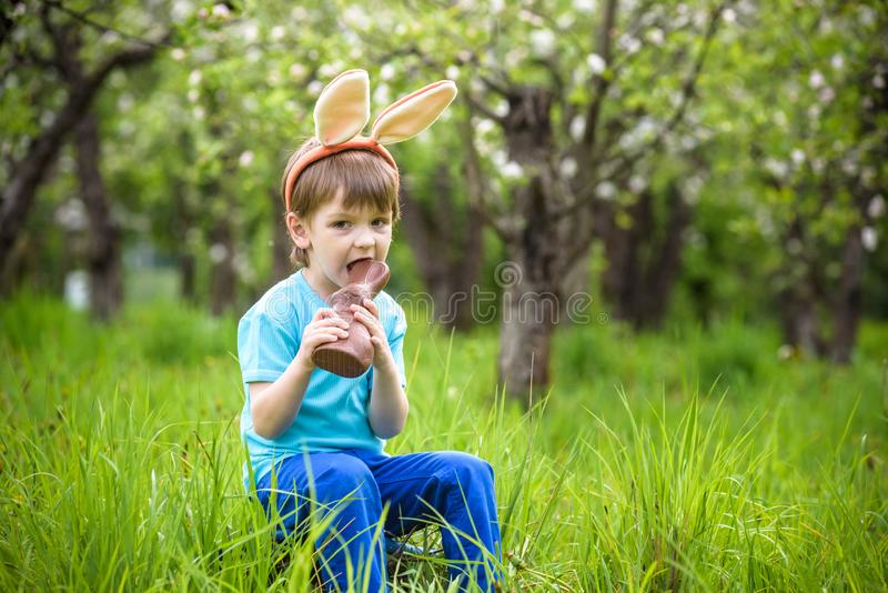 Lycklig liten litet barnpojke som äter choklad och bär öron för påskkanin som sitter i blommande trädgård på varm solig dag fira arkivfoto
