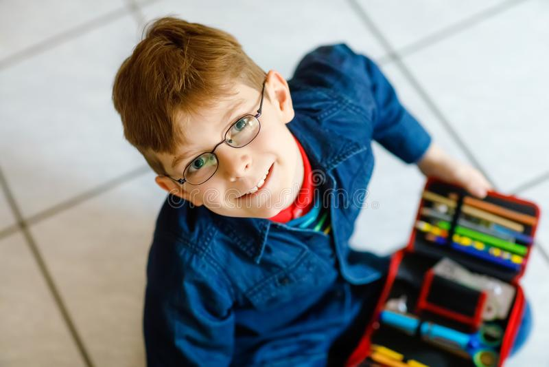 Lycklig liten skolaungepojke som med blyerts söker för ett fall för penna Det sunda skolbarnet med exponeringsglashastiga greppet fotografering för bildbyråer