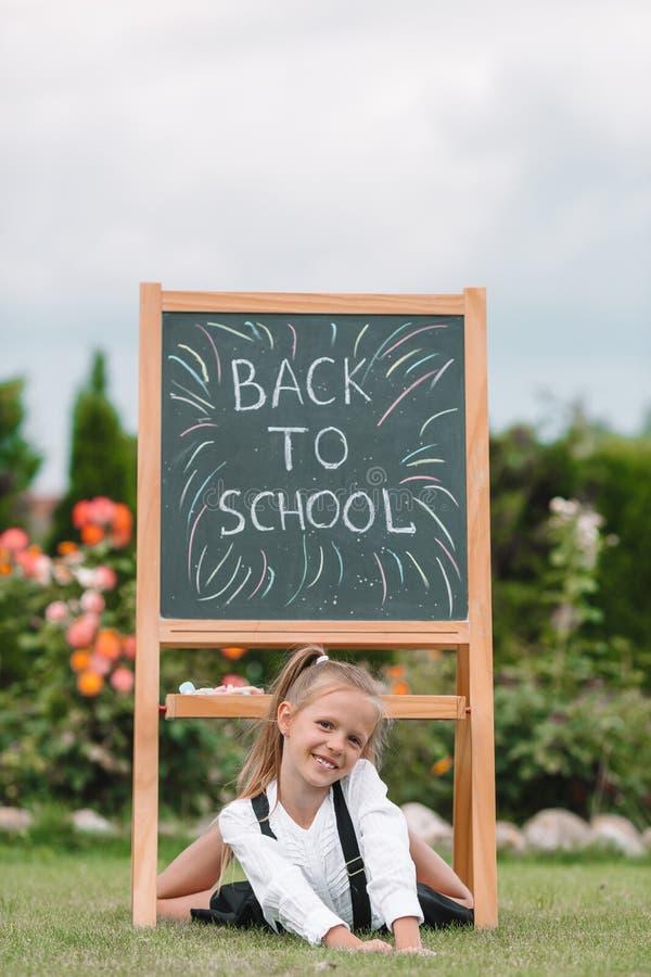 Lycklig liten skolflicka med en utomhus- svart tavla arkivbilder